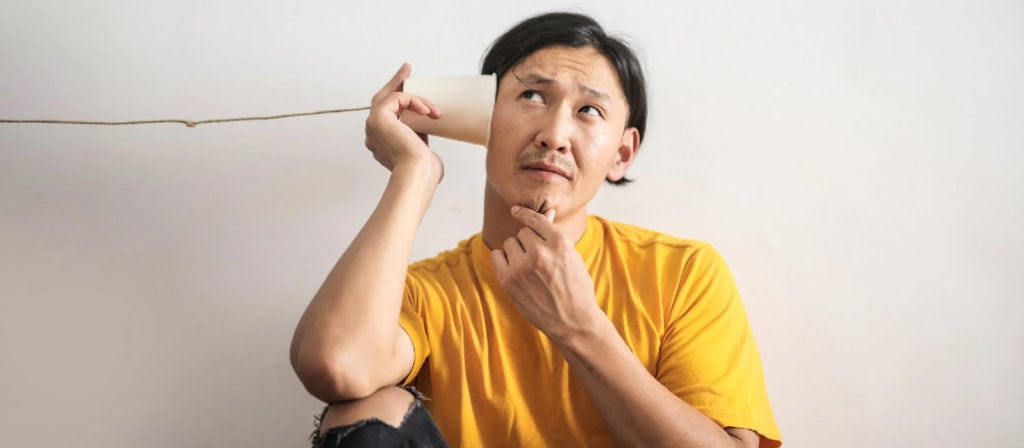 Man putting a cup with a string to his hear
