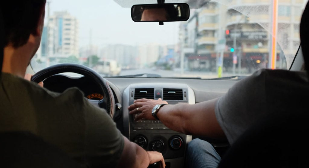 two guys inside a car driving