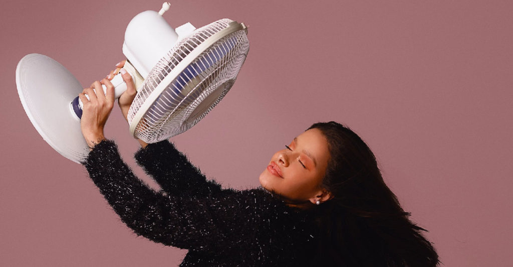 Woman directing a fan to her face