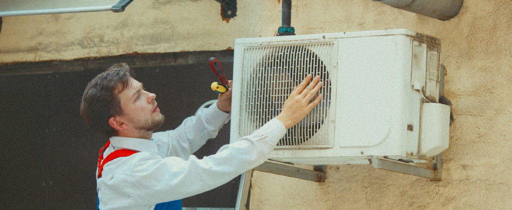 Man fixing an outside air conditioner