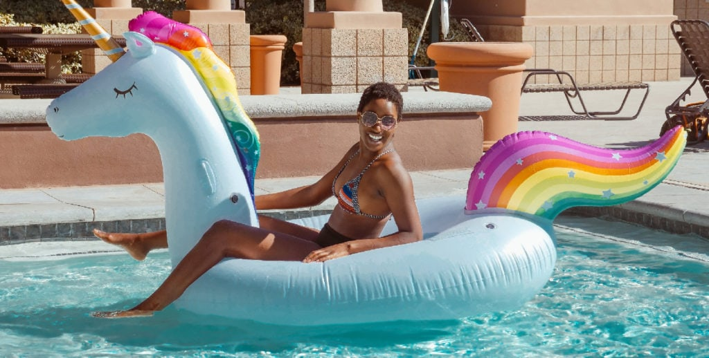 woman riding a unicorn floatie in a swimming pool