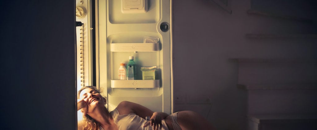 woman cooling herself with a refrigerator